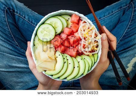 Girl in jeans holding vegan watermelon poke bowl with avocado cucumber mung bean sprouts and pickled ginger. Top view overhead