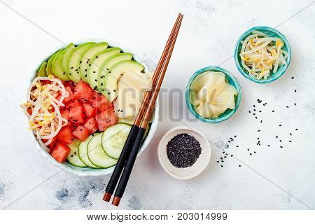 Hawaiian watermelon poke bowl with avocado cucumber mung bean sprouts and pickled ginger. Top view overhead flat lay copy space