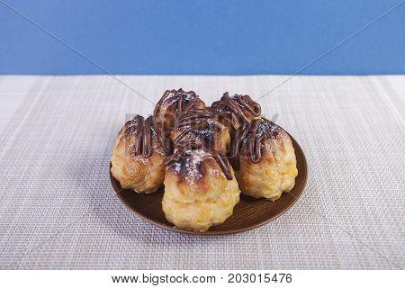 Chocolate cream puff on wooden background .