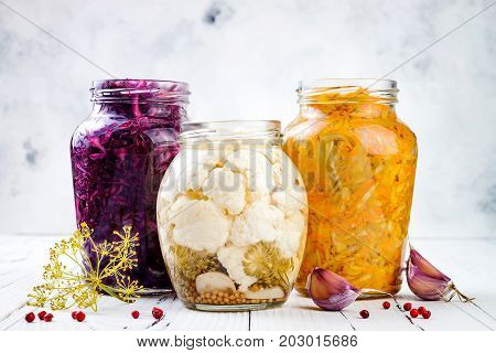 Sauerkraut variety preserving jars. Homemade red cabbage beetroot kraut turmeric yellow kraut marinated cauliflower pickles. Fermented food.