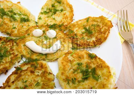 Fritters from a zucchini with a funny face on a white plate