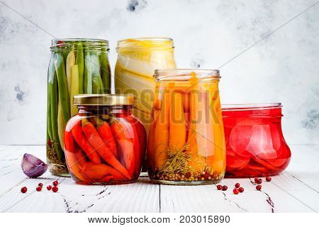 Marinated pickles variety preserving jars. Homemade green beans squash radish carrots red chili peppers pickles. Fermented food.
