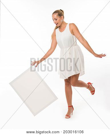 Young jocular woman portrait of a confident businesswoman showing presentation, pointing placard gray background. Ideal for banners, registration forms, presentation, landings, presenting concept.