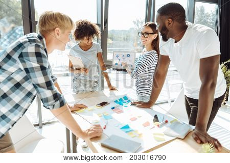 Trace the tendency. Cheerful enthusiastic young people discussing their business project and working together while expressing their ideas