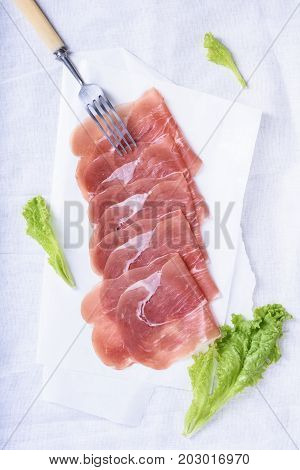 Jamon spanish ham. Slices of prosciutto crudo with salad leaves on white. Top view.