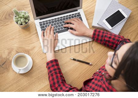 Young girl writing a blog on laptop while sitting at wooden desk with cup of coffee and smartphone