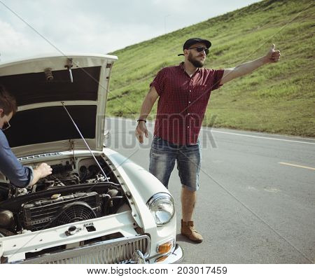 Man Hitch Hiking on The Street Side Near The Broke Down Car