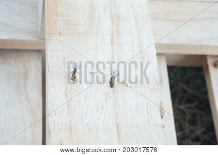 Close up of a metal nail in a block of wood plank.