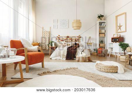 Big comfy orange chair in a bright spacious bedroom