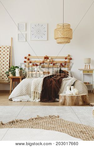 Big hand-made bed with warm blankets thrown on it