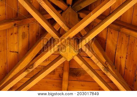 A wooden roof truss seen from the center of the room.