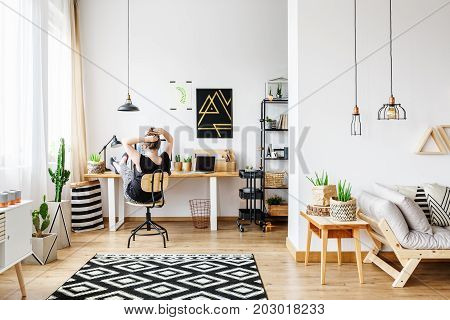 Young freelance woman working remotely at designer home in cozy white office room with pendant lamps white wall big window comfy couch and aloe plant standing on wooden retro table