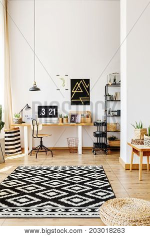 Modern atelier of creative hipster with desk computer storage cart and patterned black and white rug lying on hardwood floor