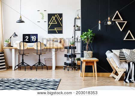 Stylish black and white nordic style open space apartment with wooden furniture office workspace with desk and computer and spacious living room with beige sofa and triangle shelves