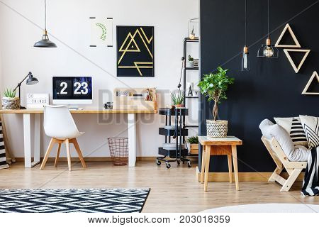 Nordic natural interior in stylish open studio for a freelancer with sofa black wall and office space with desk and black accent