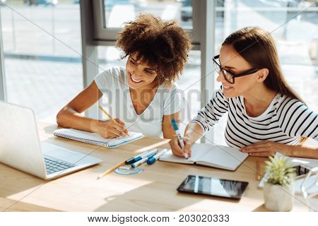 Study with pleasure. Positive young female students using their laptop and doing home assignment while preparing for classes