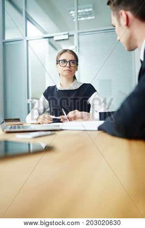 Young office manager talking to her co-worker at start-up meeting
