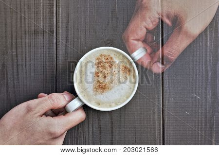 real and imaginary hand with a cup of frothy cappuccino and a heart symbol from cinnamon / memories of your favorite moments