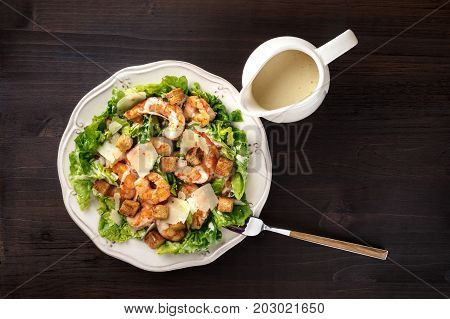 Shrimp Caesar salad with Parmesan cheese, croutons and lettuce, with a fork and a gravy boat, shot from above on a dark rustic background texture with a place for text