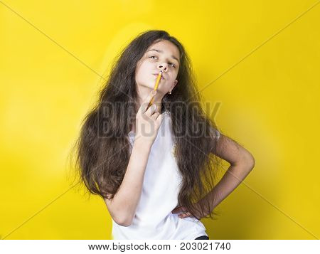 Portrait Puzzled Young Girl Thinking With A Pencil