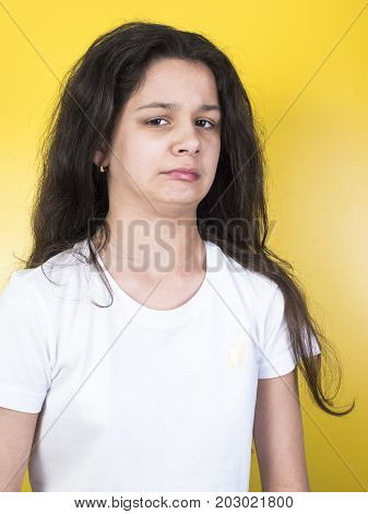 The teenage girl disgusted face expression. Yellow background.