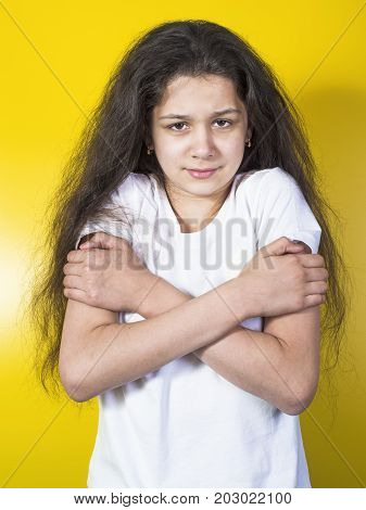 Young woman having a cold. Yellow background.