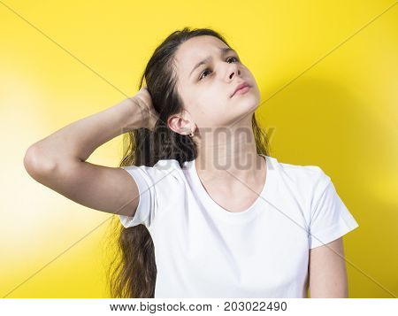 Sad brunette looks up. Close-up. Yellow background.
