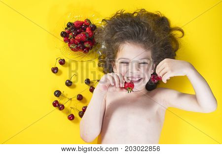 Funny And Happy Kid Eating A Berries. Kid Lies On The Yellow Background .dark Hair, Pigtails. Strawb