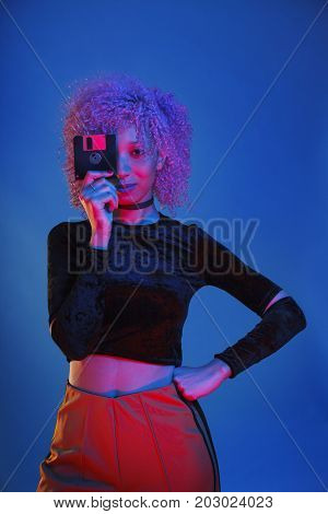 isolated woman holding an obsolete diskette from the nineteens to storage data