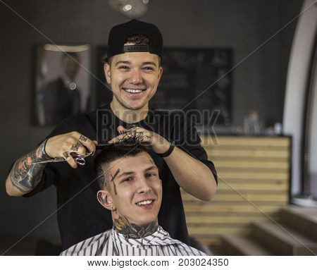 Making haircut look perfect. Young man getting haircut by happy barber while sitting in chair at barbershop