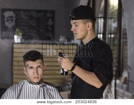 Making haircut look perfect. Young man  is prepared to get haircut by  barber while sitting in chair at barbershop