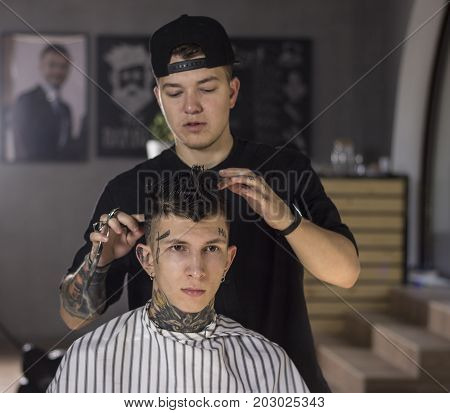 Making haircut look perfect. Young man getting haircut by barber while sitting in chair at barbershop