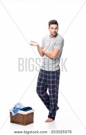 bewildered young man with basket of laundry isolated on white