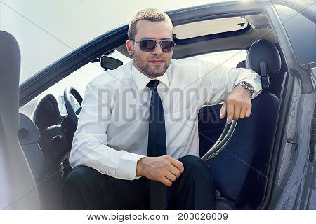 haa man in a suit, sitting in a gray car, on a sunny dayndsome man sitting in a gray blue car