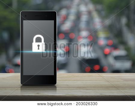 Key icon on modern smart phone screen on wooden table over blur of rush hour with cars and road Business internet security concept