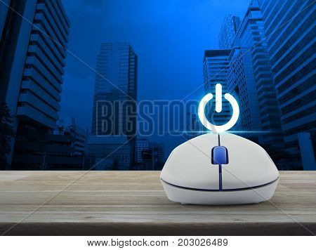 Power button with wireless computer mouse on wooden table over modern office city tower Start up business concept
