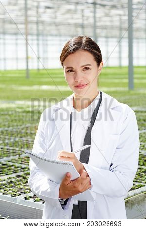 Young researcher in uniform writing down results of scientific analysis of her studies