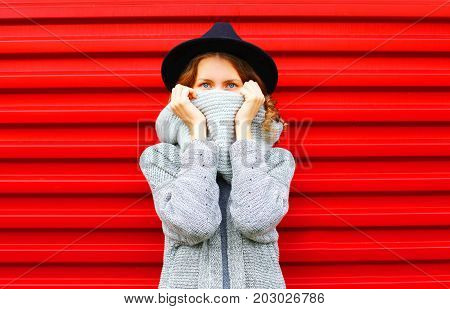 Fashion Autumn Portrait Woman Hides Her Face Scarf On A Red Background