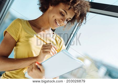 Put it down. Cheerful young curly afro american woman making notes in her notebook and smiling while feeeling happy
