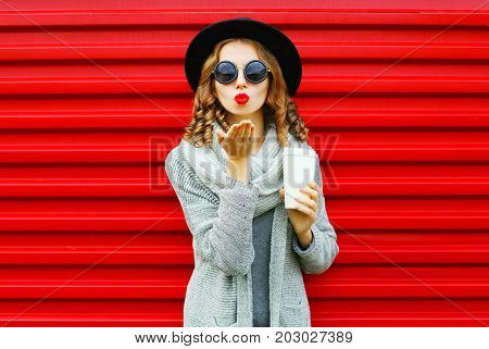 Fashion Portrait Pretty Woman With Coffee Cup Blows Red Lips Sends An Air Kiss On A Red Background