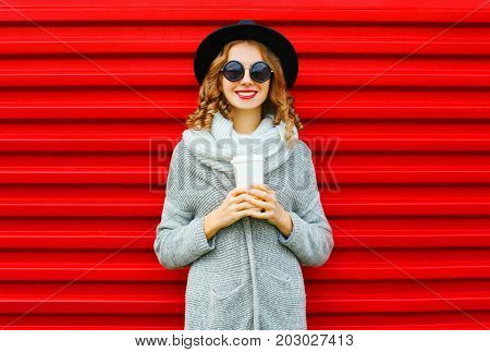 Fashion Portrait Smiling Woman With Coffee Cup On A Red Background
