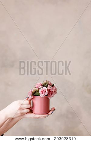 Beautiful pink roses in crimson cup holding in hands on beige background. Concept of love, romantic gift and flower decoration, holidays and congratulations, free space