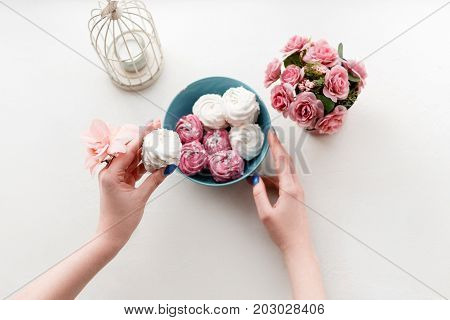 Young woman tastes colorful sweet zephyrs on teal plate. Delicious confectionery and gourmet cookies, homemade dessert for sweet tooth people, top view