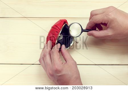 viewing through a magnifying glass a slightly opened red purse with one coin / small last savings