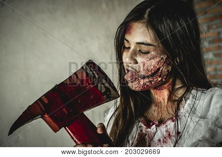 Asian girl dress killer to Halloween festival She holds a giant axe soaked with blood with scary eyes ready to kill people.