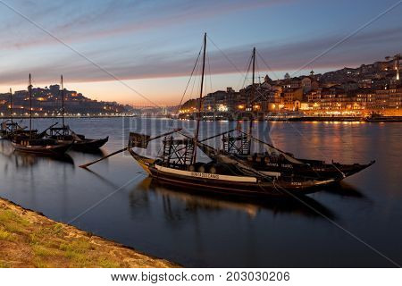 PORTO, PORTUGAL - 07.10.2016, old town cityscape on the Douro River with traditional Rabelo boats, with barrels advertising Porto alcohol