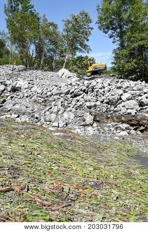 Engelberg Switzerland - 30 July 2017: digger who rearranges a bed of a river after a landslide at Engelberg on the Swiss alps