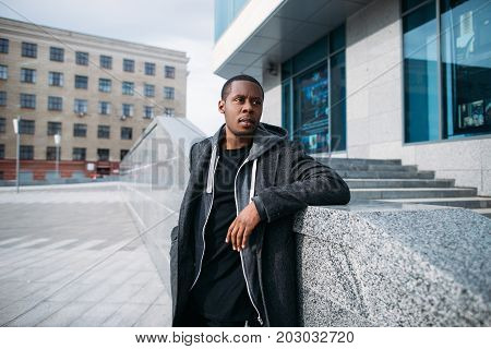 Stylish black hipster. Street fashion. Thoughtful looking African American man in selective focus, pensive male model on urban backdrop, beauty concept