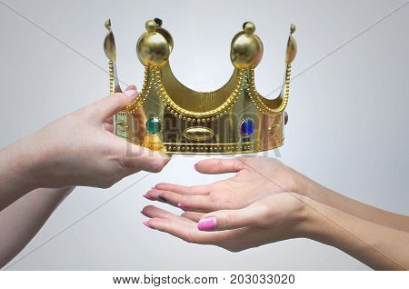 Hands gives the golden crown as symbol of power to another person. Power shift. Change of government. Lose control on situation.