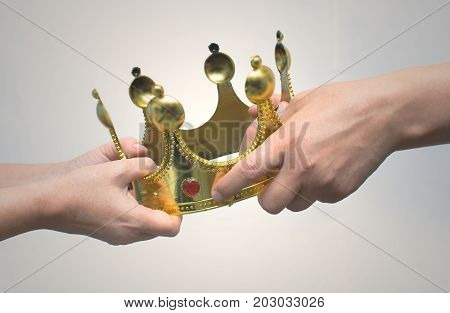 Struggle for power. Race for power. Supremacy struggle. Two person pull golden crown at each other. Competition. The power struggle in the home between wife and husband.